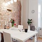 Белый стол у кирпичной стены дугообразной формы