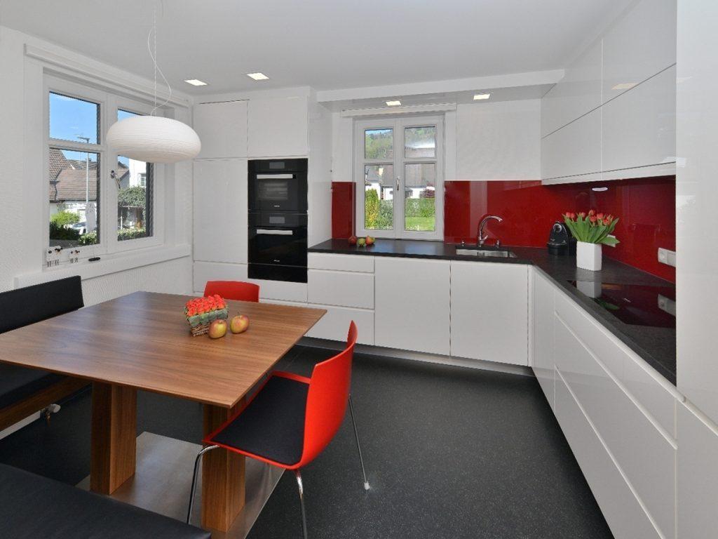 Пластиковые стулья красного цвета в современной кухне
