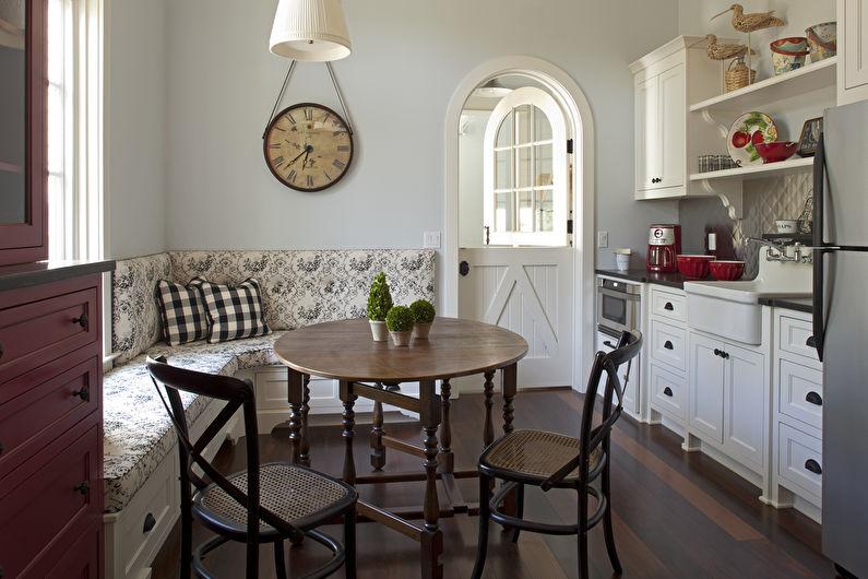 Настенные часы в интерьере кухни с диваном