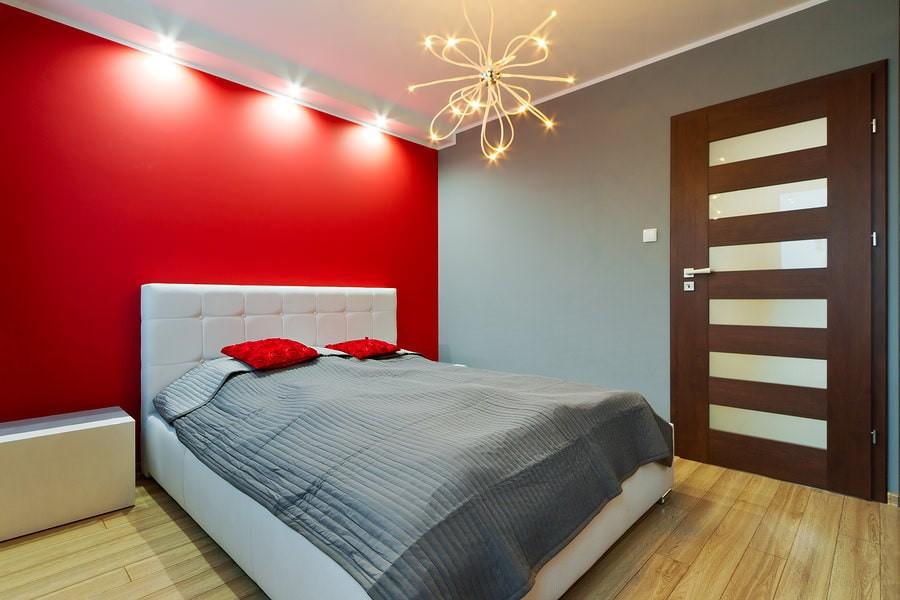 Красная стена в интерьере маленькой спальни