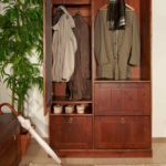 Верхняя одежда на вешалках в шкафу