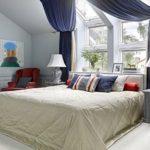 Кровать под мансардными окнами с занавесками