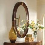 Красивые цветы в вазе около овального зеркала