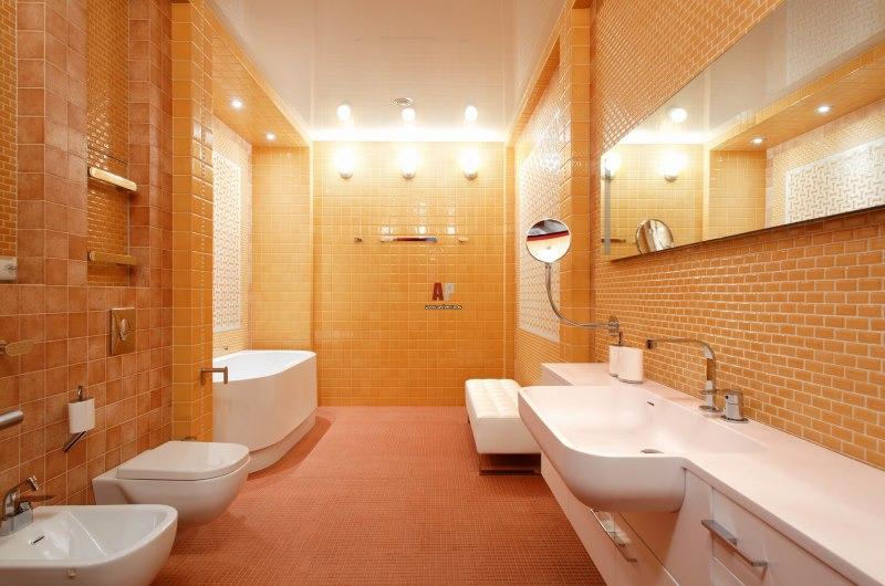 Вытянутая ванная с туалетом в оранжевых тонах