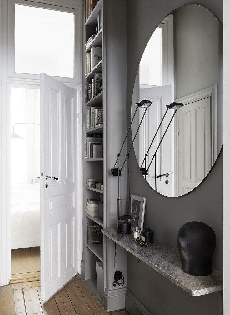 Круглое зеркало без рамы на серой стене прихожей