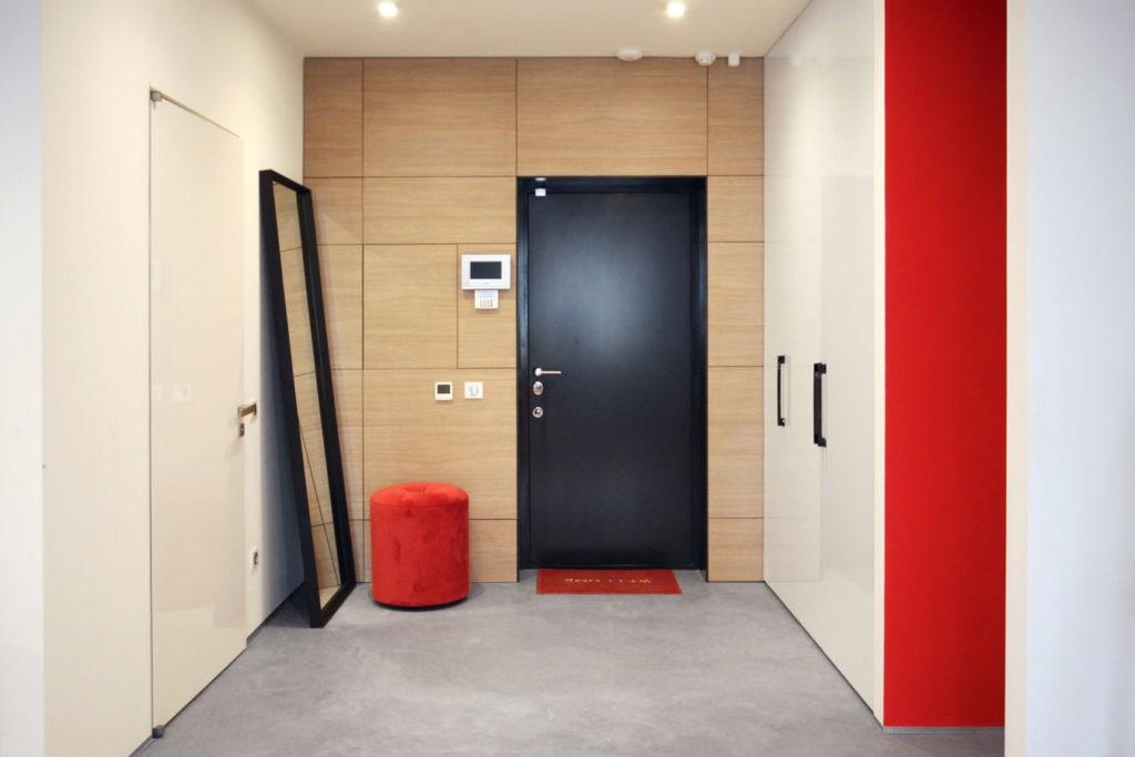 Красный пуф воле входной двери черного цвета