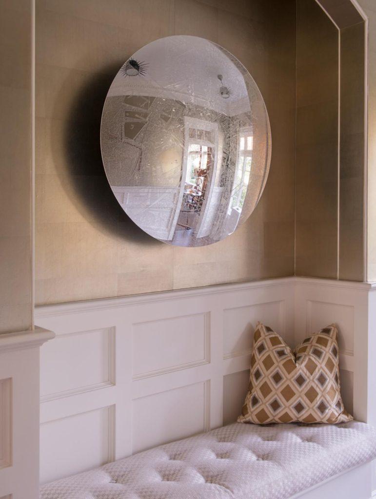Зеркало сферической формы на мягкой лавочкой в прихожей
