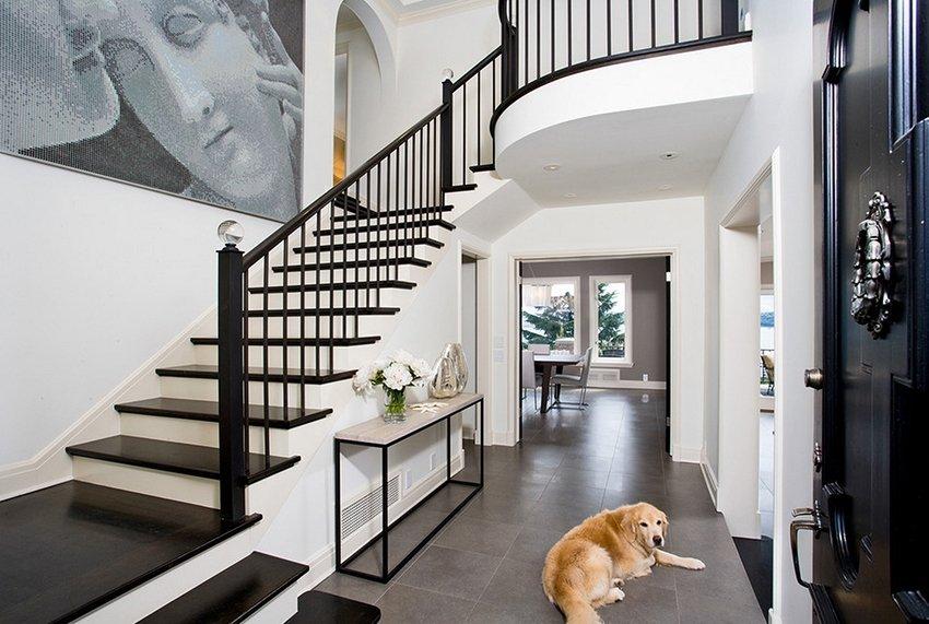 Большая собака на полу прихожей с лестницей