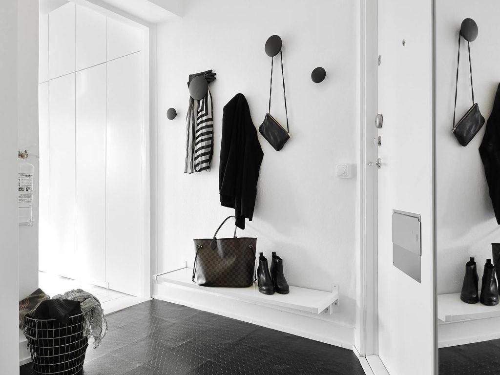 Крючки для верхней одежды на белой стене прихожей