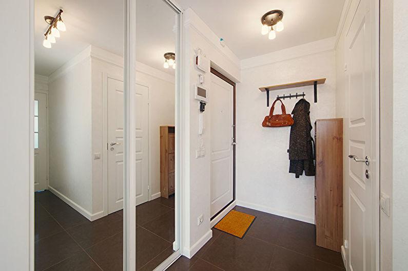 Зеркальные дверцы шкафа в интерьере белой прихожей