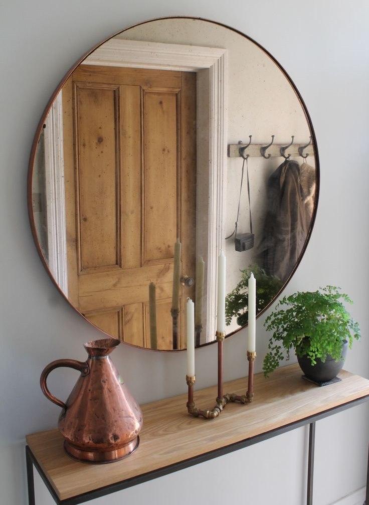 Круглое зеркало в тонкой раме напротив деревянной двери