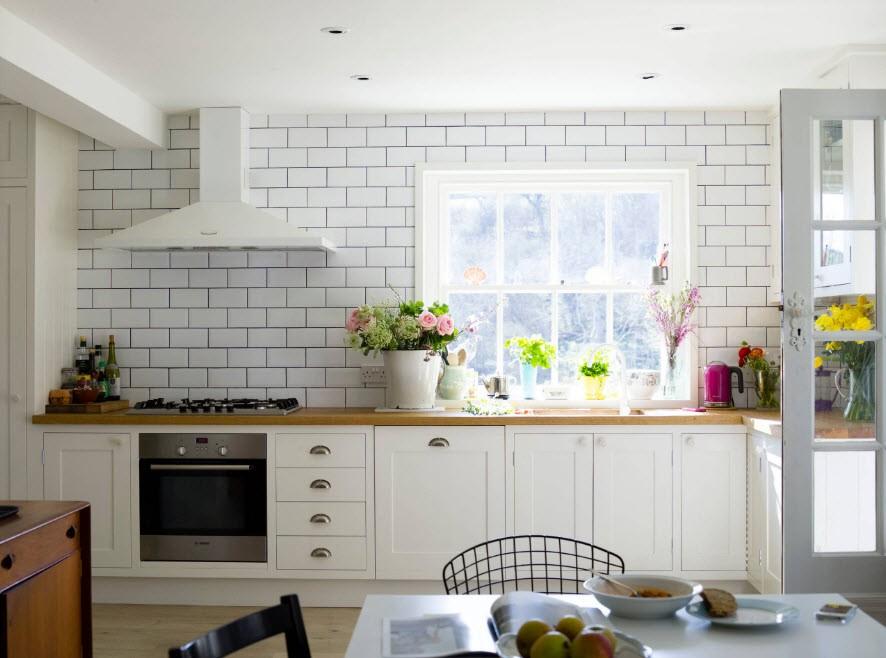 Белая купольная вытяжка в интерьере кухни без подвесных шкафов
