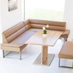Бежевый угловой диван и мягкая скамейка для обеденной зоны на кухне
