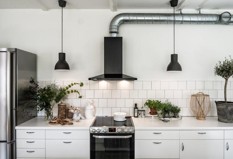 Черная вытяжка на белой стене скандинавской кухни