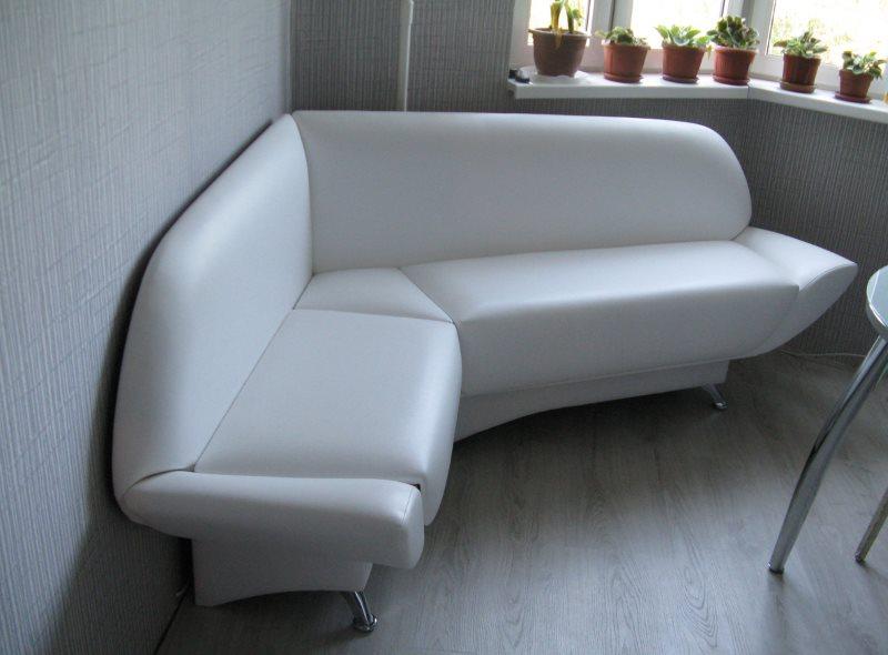 Белая обивка из кожезаменителя на угловом диване в кухне