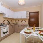 Белые шкафы на стене кухни