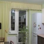 Белый холодильник около окна с балконной дверью