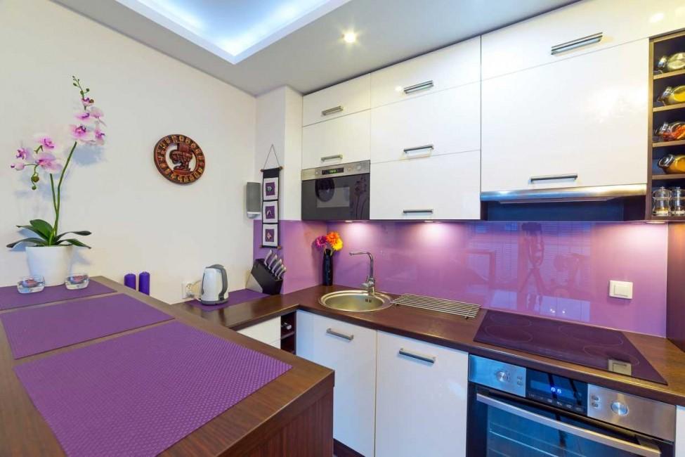 Белые шкафы над сиреневым фартуком в маленькой кухне