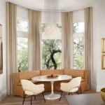 Кухонный диван необычной формы возле больших окон