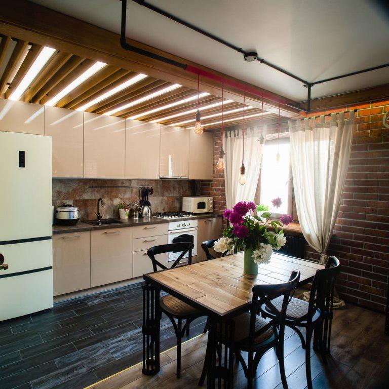 Деревянные балки на потолке кухни с бежевым гарнитуром