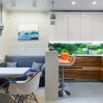 Маленький синий диванчик для кухни с кирпичной кладкой
