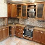 Металлическая вытяжка и печка на деревянной кухне
