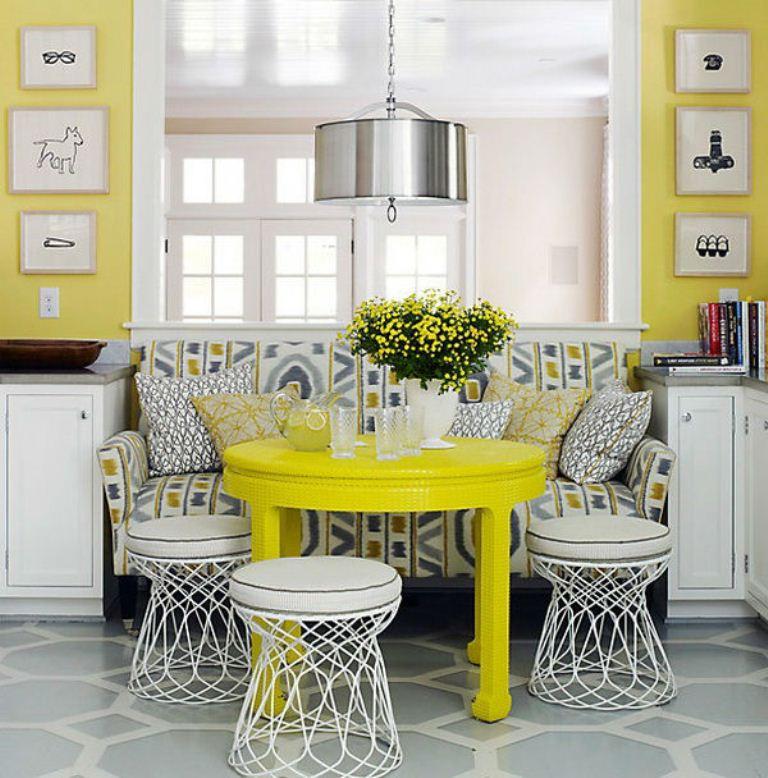 Желтый обеденный стол около дивана с пестрой обивкой