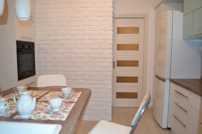 Размещение холодильника у двери в компактной кухне