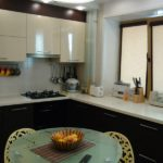 Угловая двухцветная кухонная мебель со шкафчиками под окном