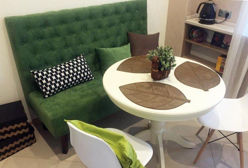 Зеленый диван с высокой спинкой в маленькой кухне
