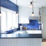 Белая мебель на кухне с синей плиткой