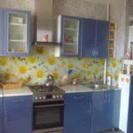 Бело-голубая кухня с ярким цветочным фартуком