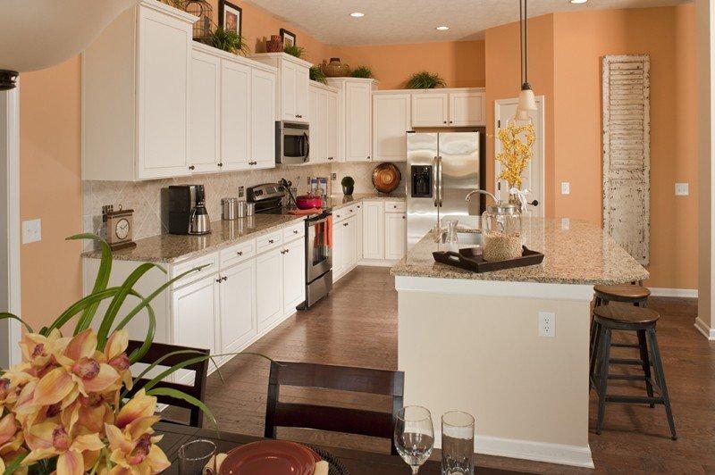 Белая мебель в кухне со стенами персикового цвета