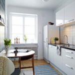 Белоснежная кухня с полукруглым столом возле акцентной стены
