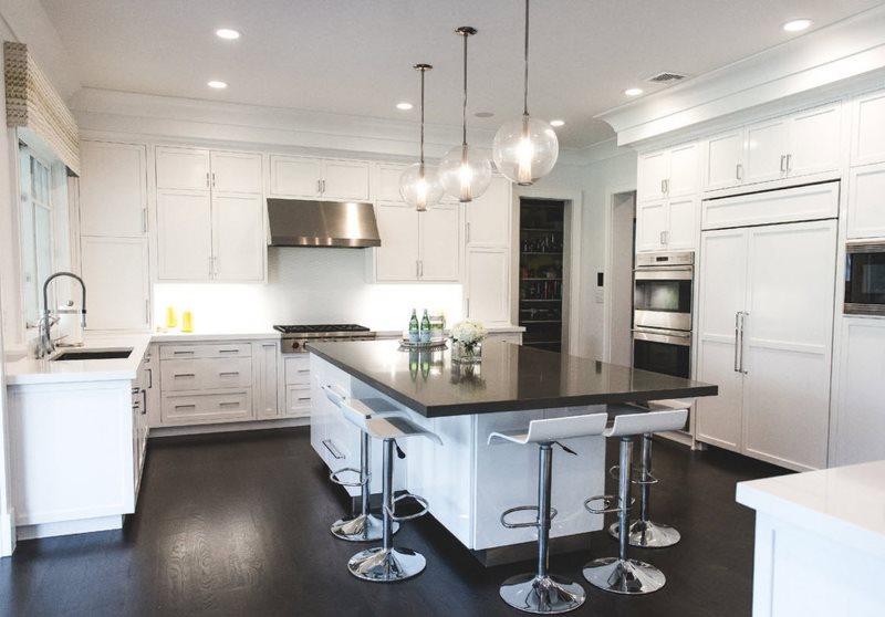 Черная поверхность кухонного острова и белая мебель