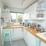 Белый гарнитур с деревянной столешницей для кухни с большим количеством окон