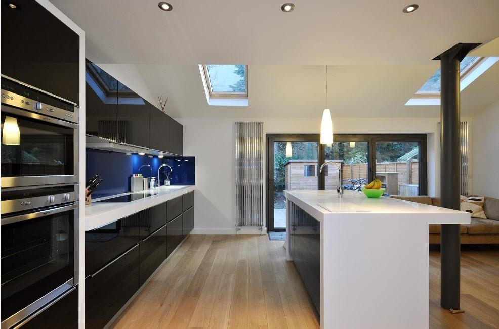 Линейная кухня черного цвета и белый кухонный остров