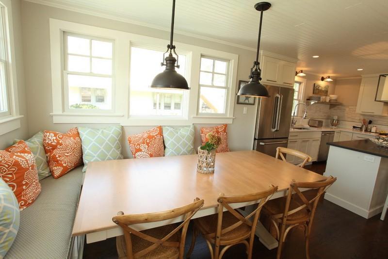 Большой обеденный стол около кухонного дивана