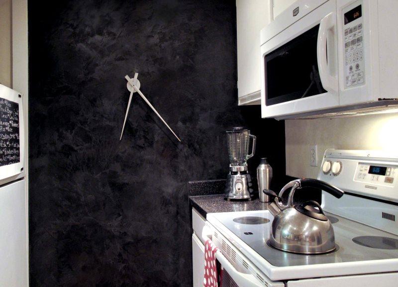 Дизайнерские часы на темной стене небольшой кухни