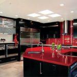 Черная кухня с красными столешницей и фартуком