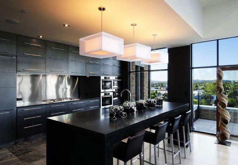 Черный кухонный остров в помещении с большими окнами