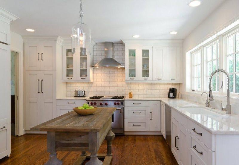 Деревянный стол в кухне с белой мебелью