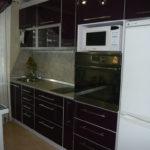 Белый холодильник в кухне с темными фасадами