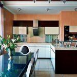 Черная мебель в интерьере кухни с персиковыми стенами