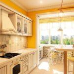 Бежевая мебель в кухне с желтыми стенами