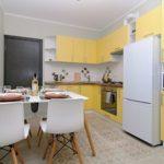 Белый холодильник в угловой кухне