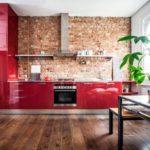 Красная глянцевая кухня возле кирпичной стенки