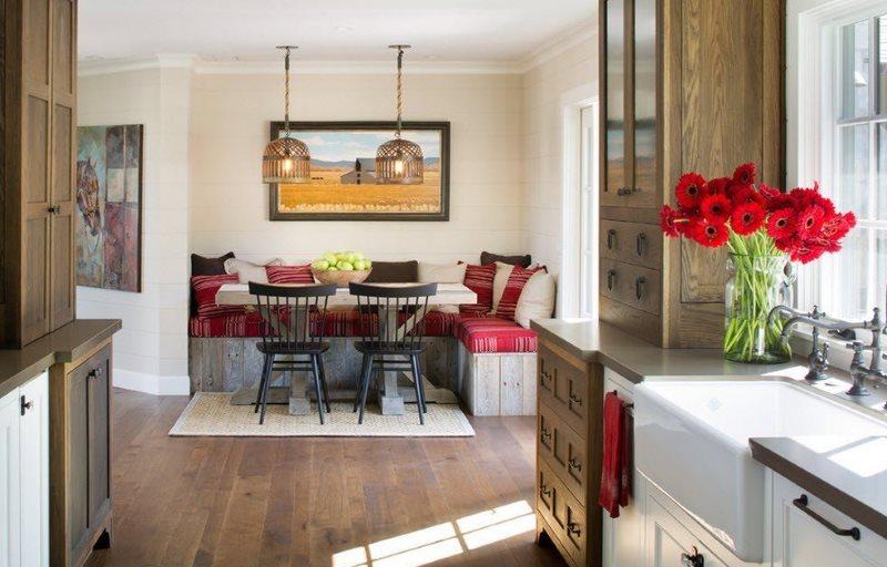 Красные цветы на подоконнике кухни с угловым гарнитуром