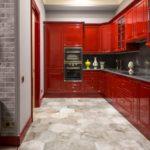Красный глянцевый гарнитур угловой формы с серым кухонным фартуком и столешницей