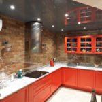Кухонный фартук из красного кирпича в сочетании с серой каменной столешницей и алым фасадом